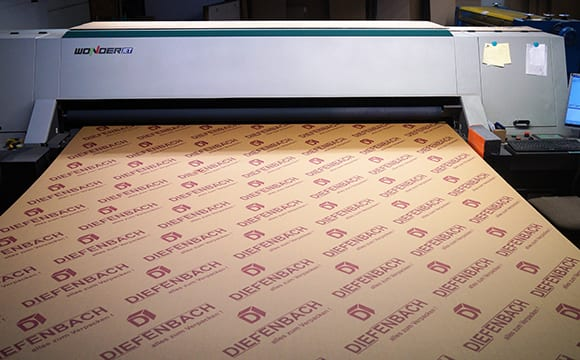 Digitaldruckmaschine beim drucken des Diefenbach Logos auf Wellpappe